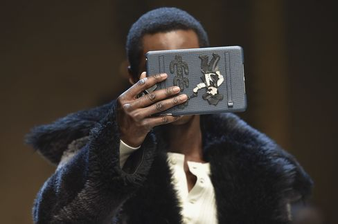 A model walks the runway, iPad in hand, at Dolce & Gabbana's fall show.