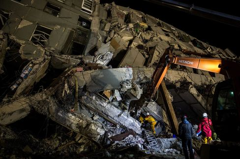 Rescue workers look for survivors in the remains of a building which collapsed in the 6.4 magnitude earthquake, in Tainan, on Feb. 8, 2016.