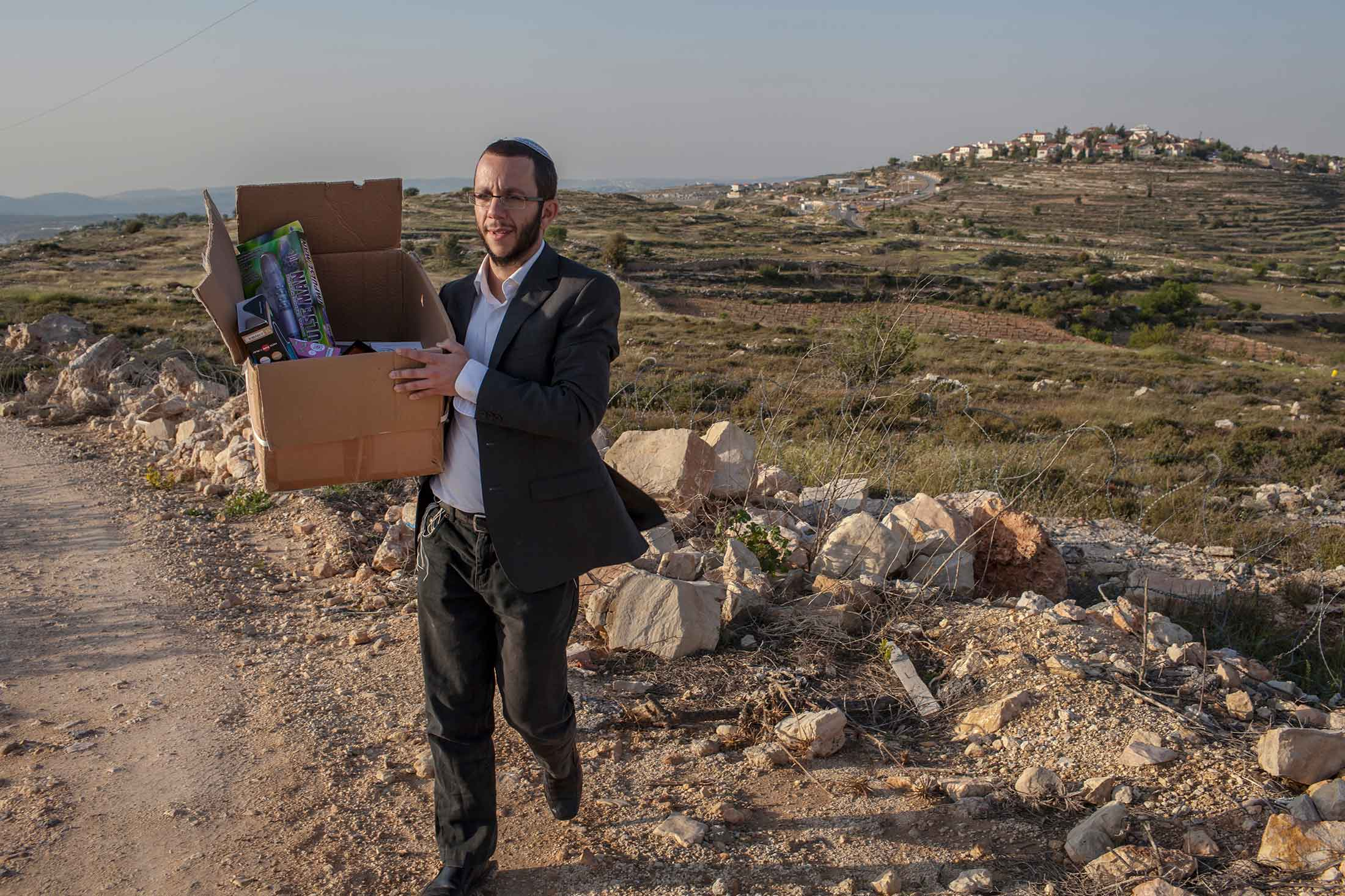 Rabbi Natan Alexander carries a box containing kosher sex toys near his home in Elazar, a Jewish settlement in the West Bank. The rabbi is careful not to expose his small children to the products sold by his e-commerce business, Better2gether, which adheres to Orthodox religious rules by banning nudity, sexy clothing, or any other suggestive imagery.