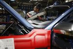 An employee works on a Ford Motor Co. Expedition sports utility vehicle (SUV) .