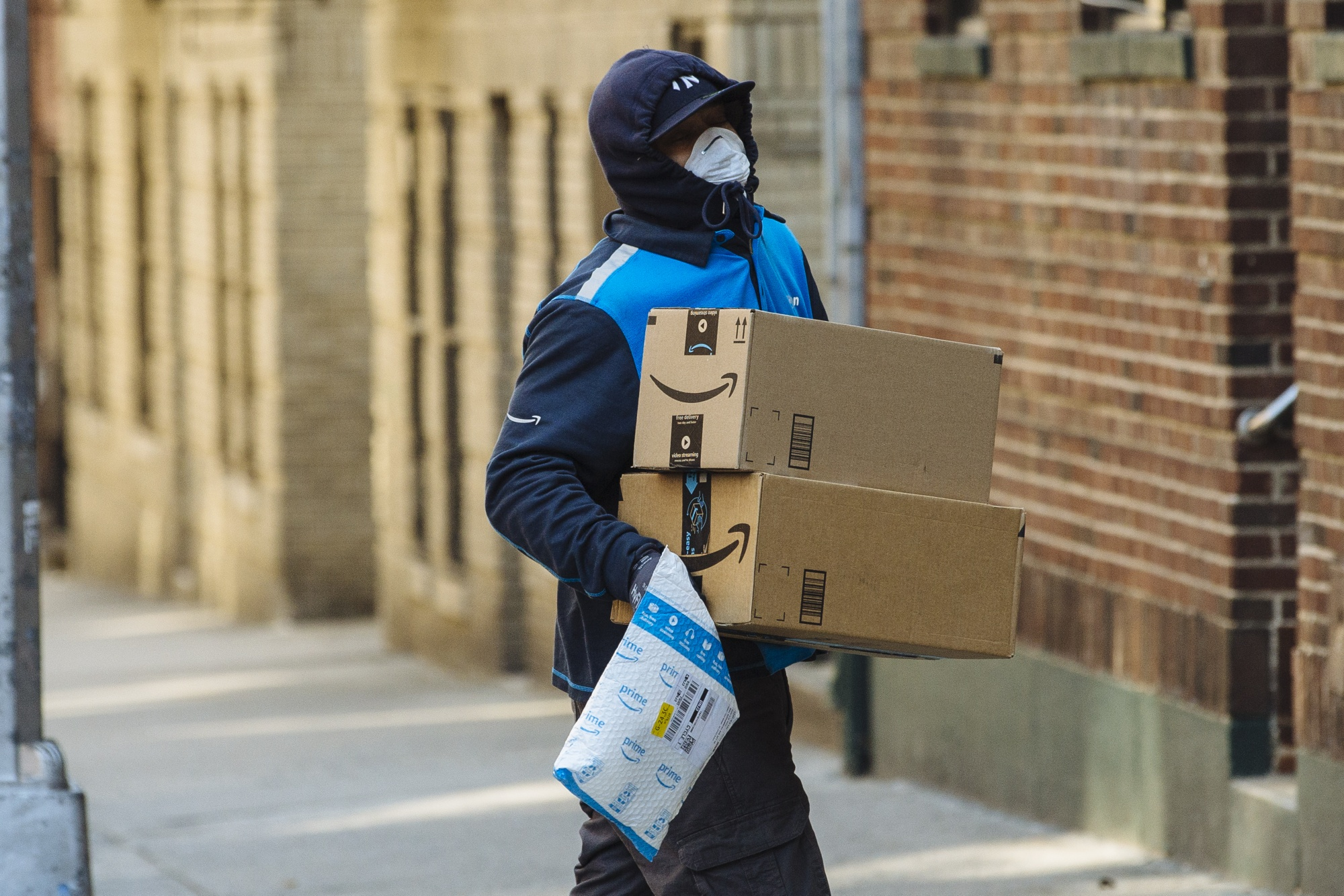 A worker carries Amazon.com Inc. boxes during a delivery in the Bronx borough of New York.
