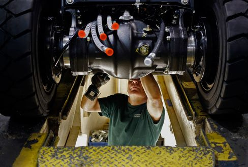 A factory worker installs components underneath a forklift on the assembly line at the Toyota Industrial Equipment Manufacturing Inc. facility in Columbus, Indiana.