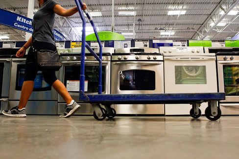 A woman pulls a cart past a General Electric Co. gas range home appliance.