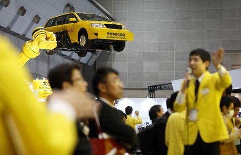 A Fanuc industrial robot lifts a vehicle during a demonstration at the International Robot Exhibition in Tokyo