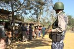 A Myanmar border guard policeman stand near a group of Rohingya Muslims in front of their homes in the restive Rakhine state on January 25, 2019.
