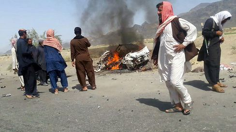 This photograph taken on May 21, 2016 shows Pakistani local residents gathering around a destroyed vehicle hit by a drone strike in which Afghan Taliban Chief Mullah Akhtar Mansour was believed to be travelling in.