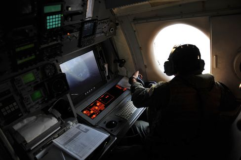 A search and rescue personnel looks out the window of a U.S. patrol aircraft searching the area in the Mediterranean Sea.