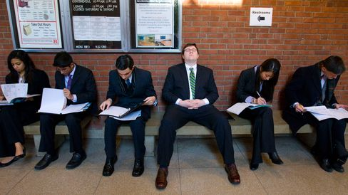 Job seekers look over their paperwork while waiting to speak to recruiters at a Rutgers University job fair in New Brunswick, New Jersey, U.S., on Thursday, Jan. 7, 2010.