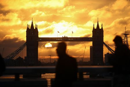 Commuters walk across London Bridge against a backdrop of Tower Bridge during sunrise in London.