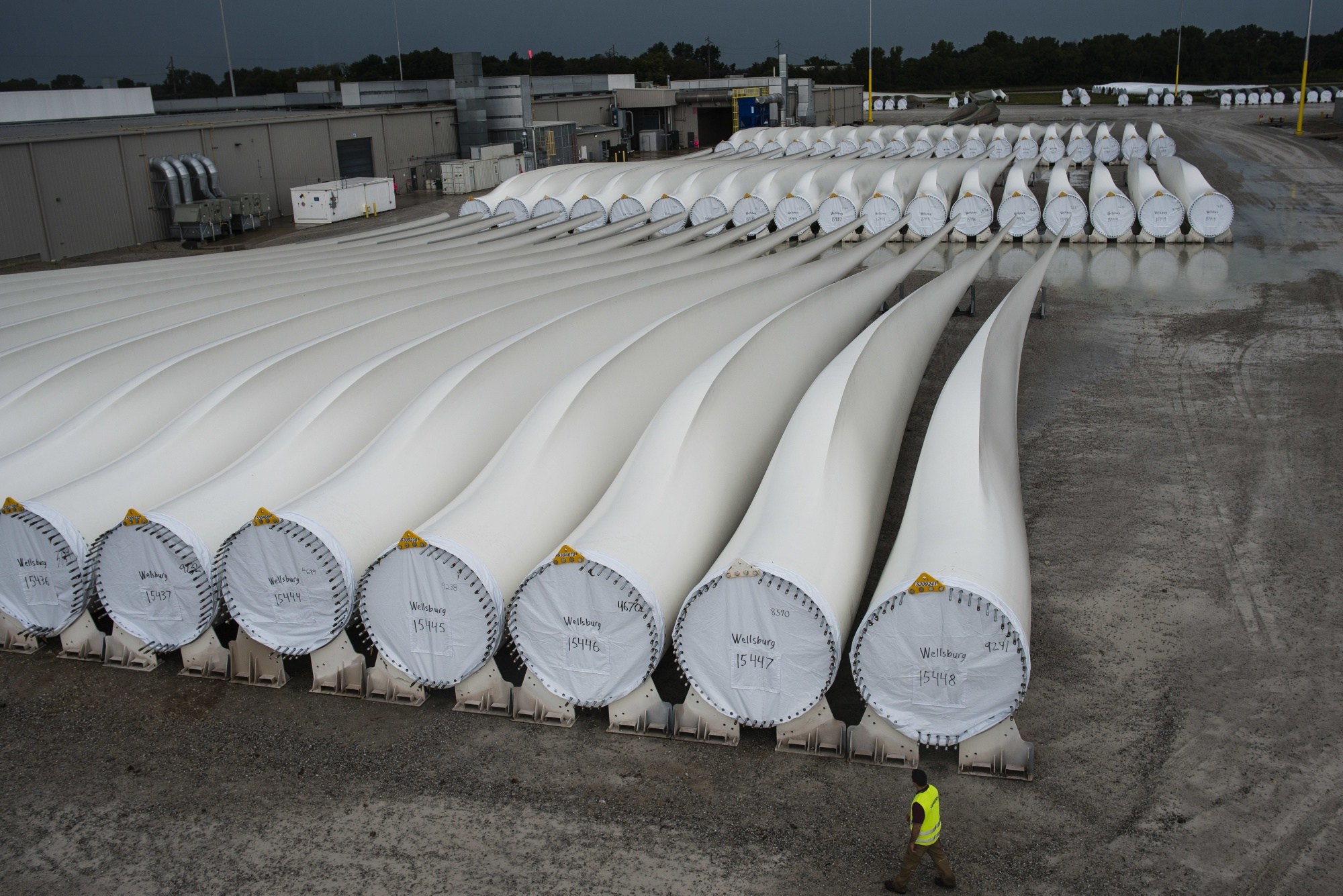 A worker walks past wind turbine blades awaiting transport in Fort Madison, Iowa.
