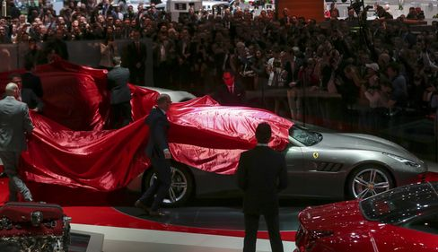 Workers remove the covers from a Ferrari GTC4 Lusso in Geneva.