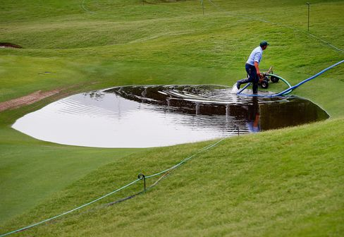 Grounds crew staff work to remove standing water on the 17th hole after heavy rains delayed Round Two of the AT&T Byron Nelson at the TPC Four Seasons Resort Las Colinas on May 29, 2015 in Irving, Texas.