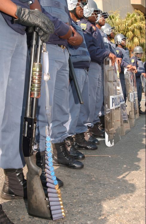 Heavily armed members of the South African public order police stand guard outside the conference centre at the start of the 2002 World Summit in Johannesburg. Monday August 26,  2002 Photographer : John Liebenberg/ Bloomberg