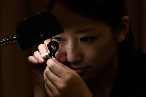 An employee inspects a used diamond ring inside the Komehyo Co. Shinjuku store in Tokyo. Photographer: Akio Kon/Bloomberg