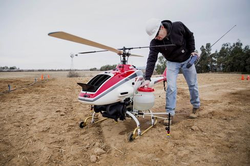 A drone operator checks over a Yamaha crop duster before a test flight at a UC Davis testing area.