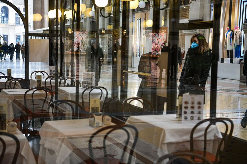 A woman wearing a protective mask stands in front of an empty bar in Galleria Vittorio Emanuele II in Milan, on March 5.