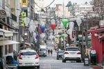 Pedestrians wearing protective face masks walk through an empty street in the Itaewon district of Seoul, South Korea, on Friday, Aug. 21, 2020.