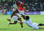 Kenya's Isaac Adimo, center, vies with Zimbabwe's Lenience Tambwera during a match that acts a qualifier for the 2019 Rugby World Cup in Japan.