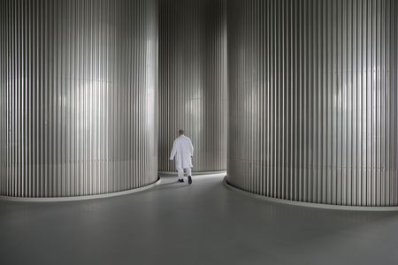 An employee passes between fermentation tanks inside the Grolsch beer brewery in Enschede, Netherlands.
