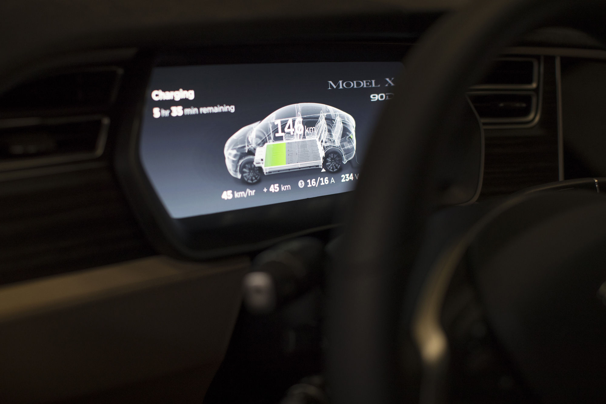 A dashboard display shows the charging status of Tesla Model X SUV battery.