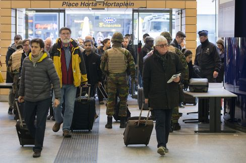 Armed soldiers stand guard as travelers enter Brussels Midi railway station on March 23.