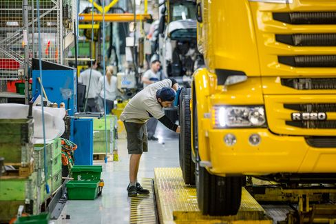 An employee works on the assembly of a Scania R520 truck as it passes along the production line inside the Scania AB plant in Sodertalje, Sweden, on March 26, 2014.