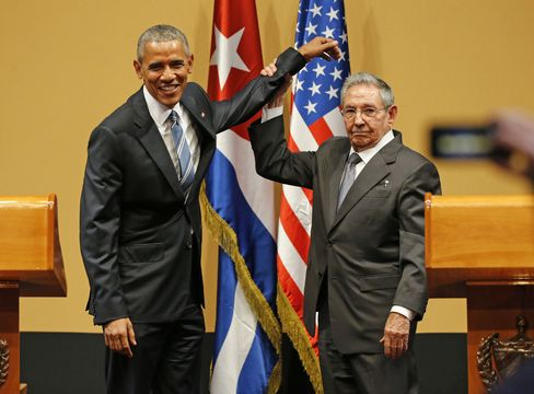 Raul Castro lifts President Obama's arm