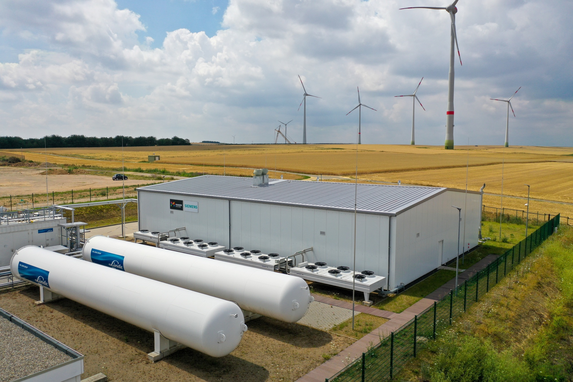 Wind turbines stand in view of a hydrogen electrolysis plant in Mainz, Germany.