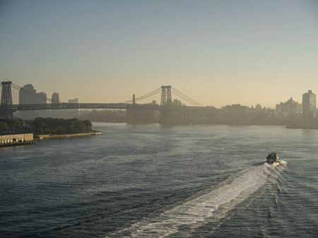 A morning glow rises behind the Williamsburg Bridge as a lone boat glides through the water. (Shot at 1/2000th, f/8, and 400iso.)