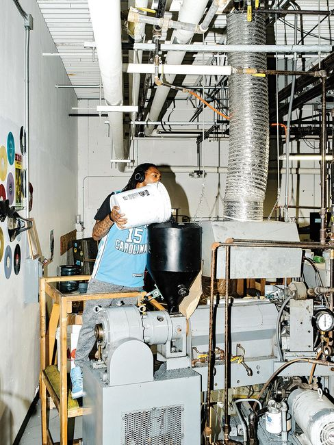2. An employee adds vinyl pellets to a record press.
