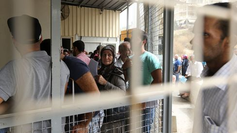 Syrian refugees queue to apply for immigration outside the German Embassy on the northern outskirts of Beirut, on September 10, 2015.