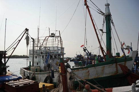 A wooden fishing boat used by a human trafficking syndicate to transport nearly 600 mostly Rohingya migrants from Myanmar and Bangladesh is seen anchored at Lhokseumawe fishing port located in Indonesia. Photographer: Chaideer Mahyuddin/AFP/Getty Images