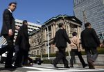 Pedestrians cross a road in front of the Bank of Japan headquarters in Tokyo, Japan.