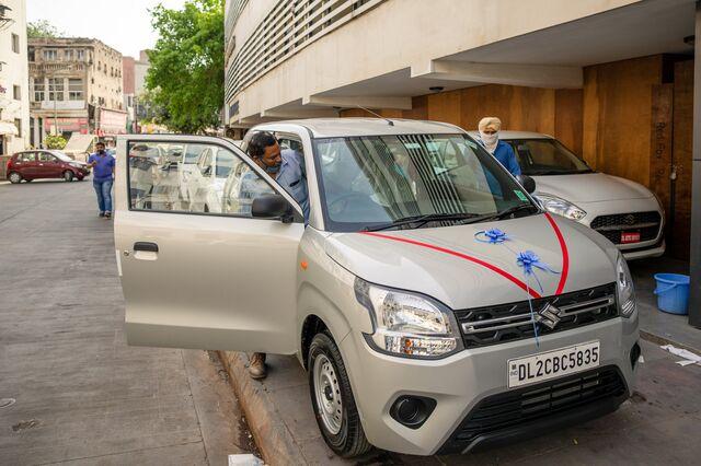 A customer inspects a Maruti Wagon R outside a Maruti Suzuki showroom in New Delhi.