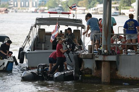 Officials bring diving equipment as police investigate the site of a second explosion at a canal near a busy train station.