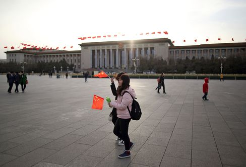 Pedestrians pass the Great Hall of the People in Beijing.