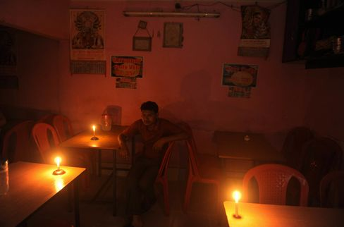 An Indian diner waits for his meal in candle light at a hotel during a power cut in Siliguri in July 2012.