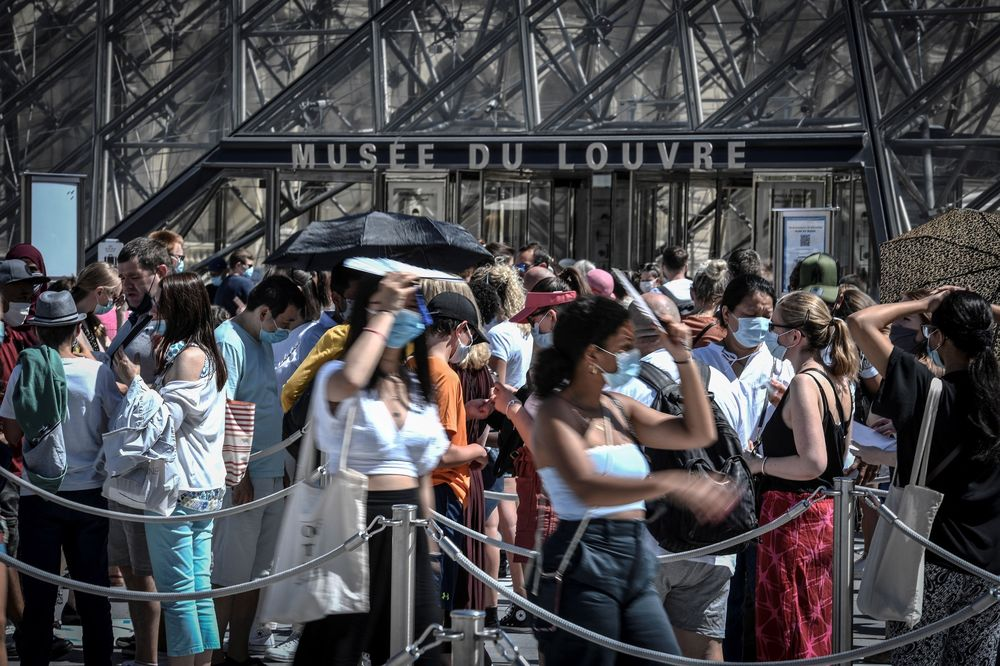 People wearing a protective face masks queue at the entrance of the Louvrein Paris on Aug. 6.