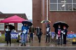 Precinct and campaign volunteers hold umbrellas while standing outside a polling station in Leesburg, Virginia.