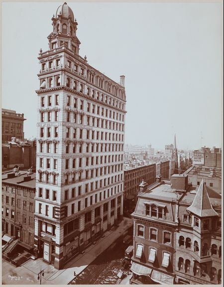 The southeast corner of Fifth Avenue and 22nd Street in New York in 1899, before the apparel industry moved to the Garment District. On the corner is a tall building housing several textile-related businesses and a piano store.