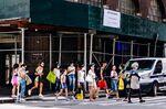 Pedestrians wearing protective masks cross a street in the Soho neighborhood of New York, U.S., on Thursday, Aug. 6, 2020.