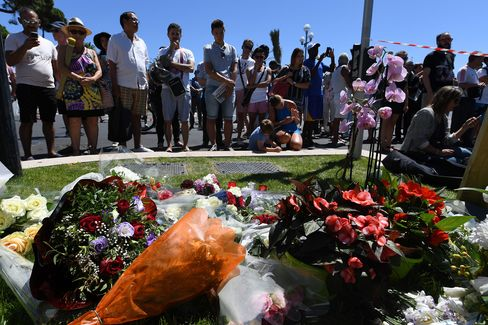 People stand in front of flower tributes in Nice on July 15.