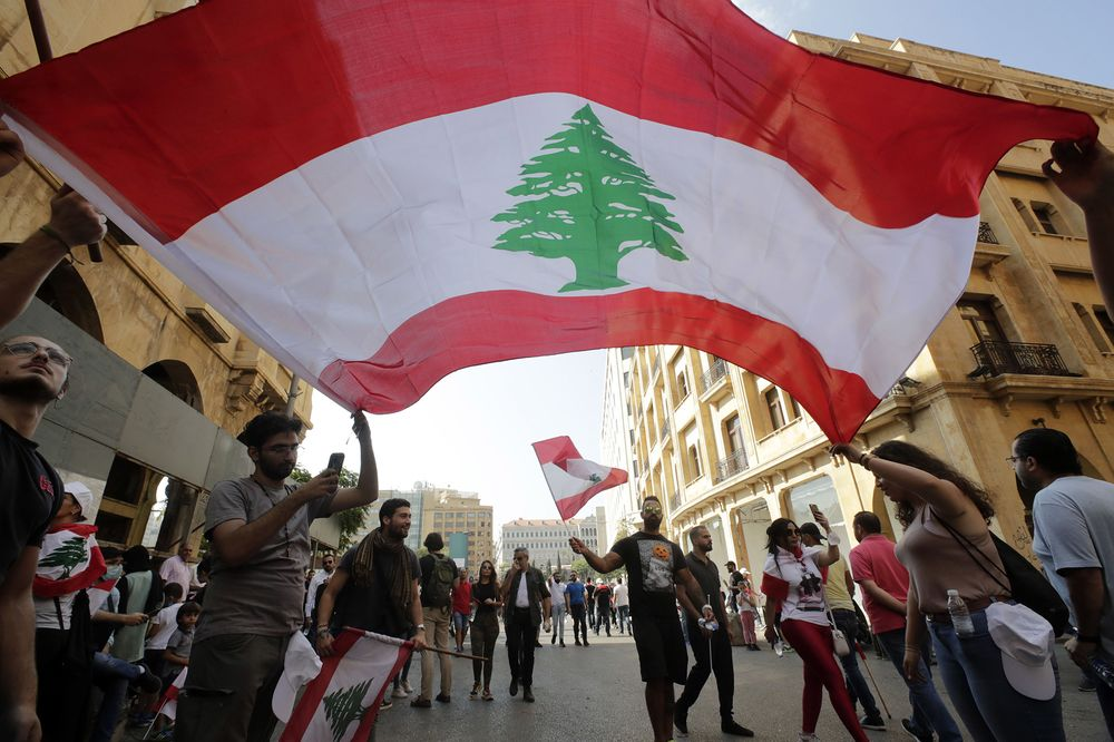 Protesters wave the national flag in downtown Beirut on Oct. 19.