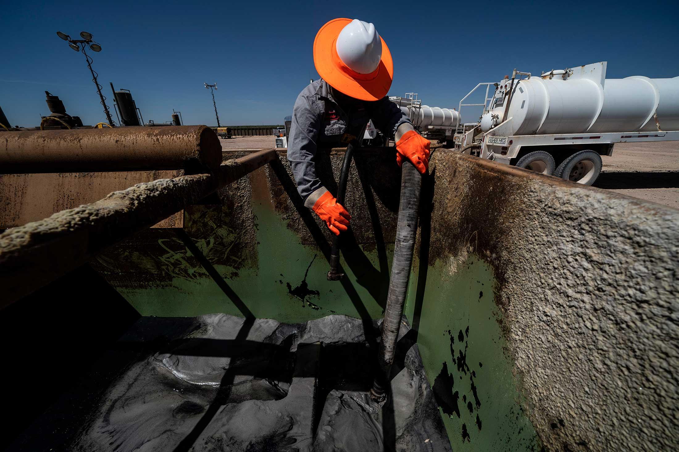 Pekerja mengekstraksi minyak dari sumur di Permian Basin di Midland, Texas.