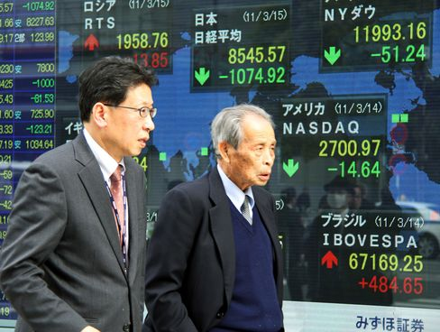 Pedestrians walk past an electronic stock board outside a securities firm in Tokyo. Commodities fell.