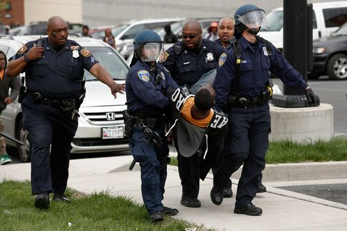 Baltimore Police officers arrest a man during a skirmish with demonstrators after the funeral of Freddie Gray on April 27, 2015.