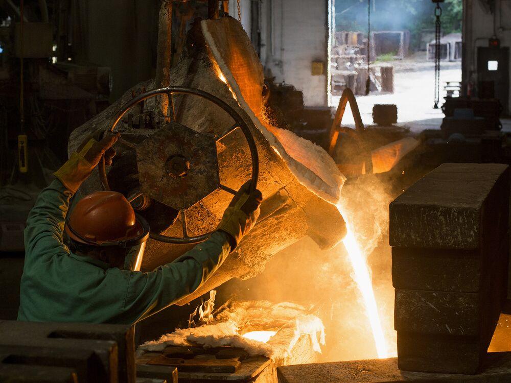 Рабочий разливает расплавленный металл из печи на литейном заводе в Салеме, штат Огайо.