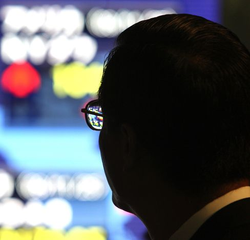 A pedestrian looks at an electronic stock board in Tokyo