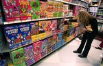 A customer browses the cereal selection at an Associated Supermarket.