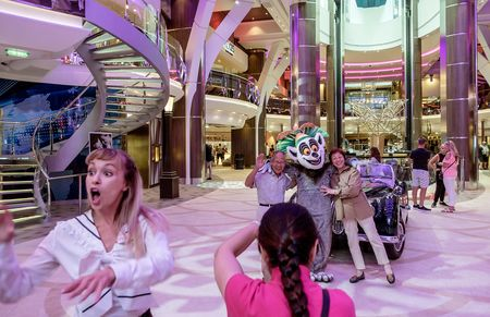"""Spread over 18 decks and seven """"neighborhoods""""—connected by 24 elevators—the Oasis-Class Harmony of the Seas is capable of accommodating close to 9,000 passengers and crew. Here, guestshave souvenir photos taken in the Royal Promenade neighborhood."""